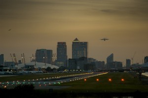 An aircraft departs London City with Canary Wharf and the O2 in the background.
